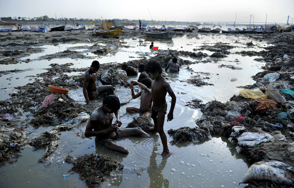 Indian men search for coins and gold in the polluted waters of the Ganga river at Sangam after the Kumbh Mela festival, in Allahabad on April 2, 2013. The two month long Kumbh Mela, celebrated every 12 years at the conjunction of two sacred rivers on the outskirts of the northern Indian city of Allahabad, drew massive crowds of devotees, ascetics and foreign tourists till its conclusion on March 10. AFP PHOTO/SANJAY KANOJIA