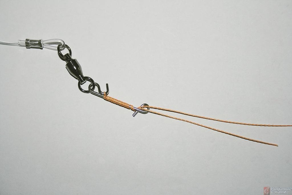 Накиньте петлю из основной лески на крючок безузлового соединителя. Оберните сложенную вдвое плетёную основную леску вокруг цевья безузлового соединителя. Десяти витков достаточно для прочного соединения.