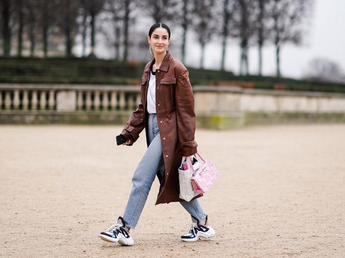 Девушка в прямых джинсах, кроссовки и коричневое кожаное пальто