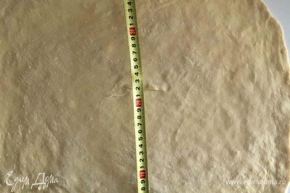 Возвращаемся к тесту. Припылив мукой рабочую поверхность сначала скалкой раскатываем тесто в круг примерно 25 см в диаметре. Затем подсовываем руки ладошками вниз под тесто, слегка сгибаем пальцы и тыльной стороной ладони начинаем растягивать тесто от центра к периферии. Когда почувствуете, что центр достаточно растянут, начинаем пальчиками растягивать края, формируя прямоугольник. Постепенно и потихоньку растягиваем, участок за участком, у меня получился прямоугольник 50/40 см примерно.