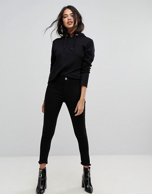 Девушка в черных джинсах скинни и толстовка и лакированные ботильоны