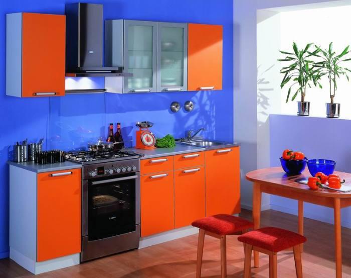 Кухня с синими стенами и красной мебелью.
