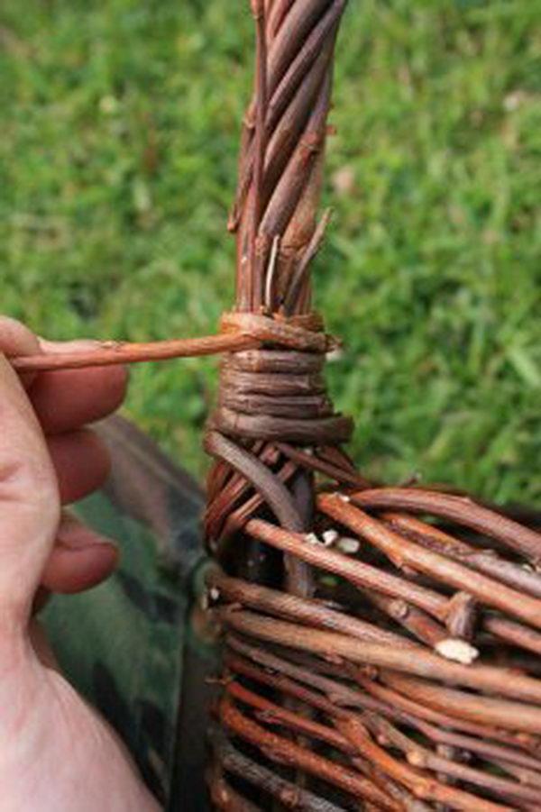 Тонкие прутья ручки загните вверх и оплетите их с каждой из сторон тонким прутом, обернув его плотными витками и пропустив конец в обратном направлении
