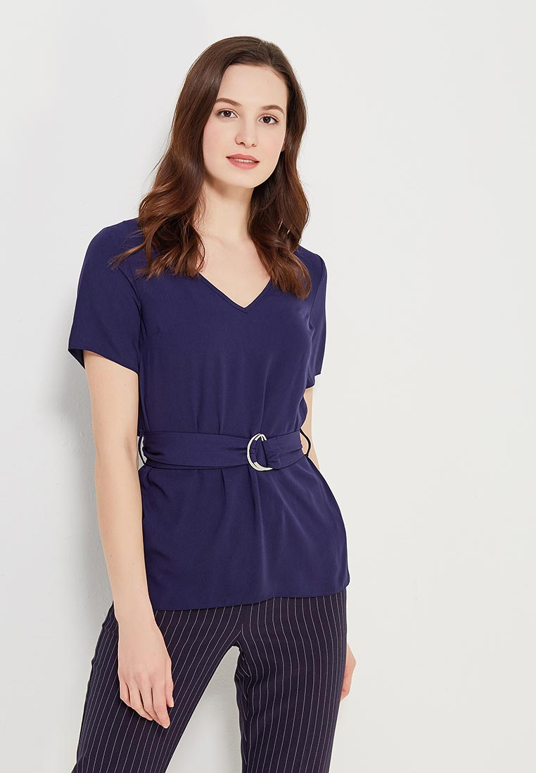Девушка в синей блузке с поясом и брюках в полоску