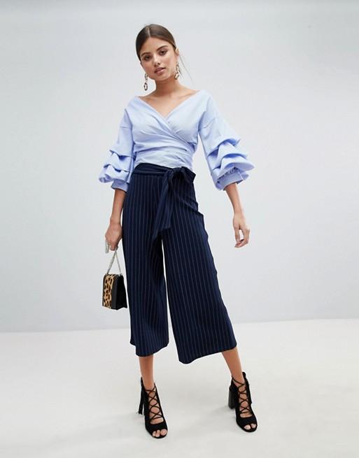 Модель в кюлотах в тонкую полоску и голубая блузк в рюшами