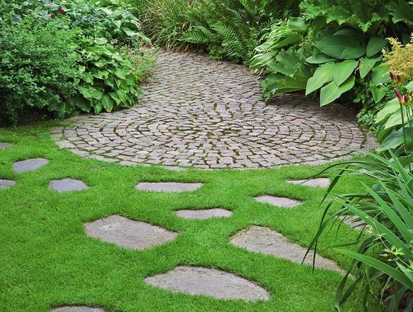 Необычная комбинация камня и газона: мощение заканчивается круглой площадкой и как бы растворяется на газоне в форме отдельно уложенных плиток из природного камня.