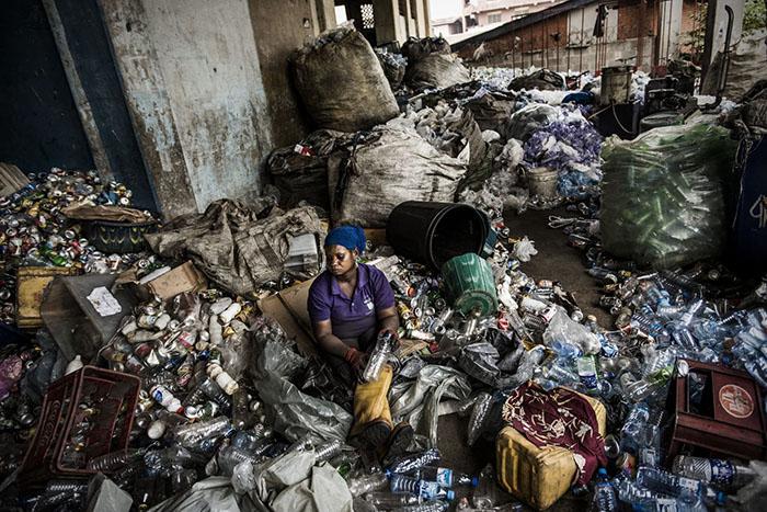 Женщина очищает бутылки от бумаги. За эту работу женщина получит жетоны, которые сможет обменять на бытовые приборы.