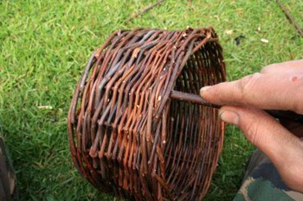 При желании вы можете сделать для корзины и ручку. Для этого гибкий и плотный прут вставьте в отверстия плетений боковых стенок корзины, предварительно заострив его концы.