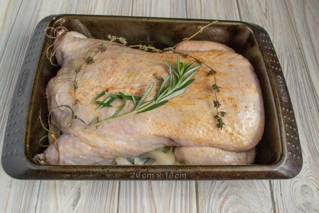 Смазываем курицу растительным маслом, натираем паприкой, кладём в форму, добавляем веточку розмарина и тимьяна