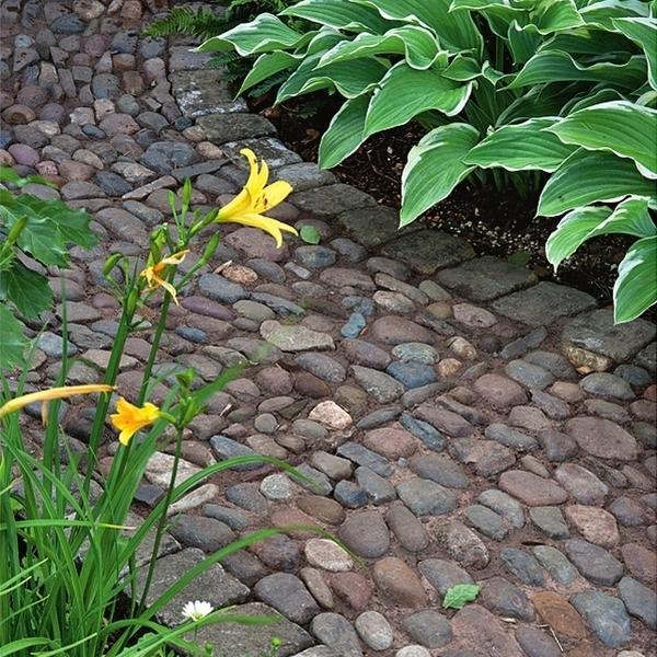 Дорожка, мощенная грубым камнем, хорошо смотрится в саду в стиле кантри