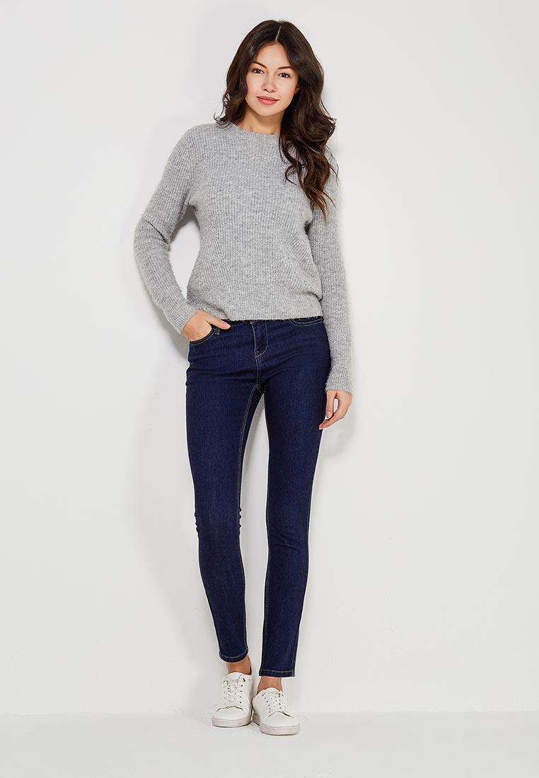 Девушка в темно синих джинсах и сером джемпере