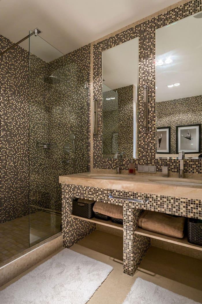 Декоративная мозаика в интерьере ванной комнаты смотрится очень красиво, особенно когда её украшают прозрачные стекла и зеркала