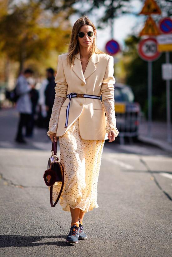 Девушка в воздушной кремовой юбке, светлый блейзер с поясом и кеды
