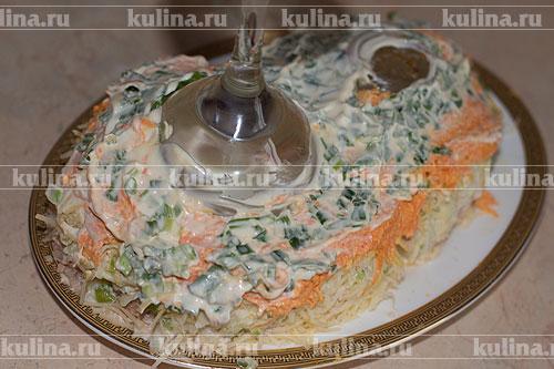 Зеленый лук мелко нарезать, выложить на салат и смазать небольшим количеством майонеза.