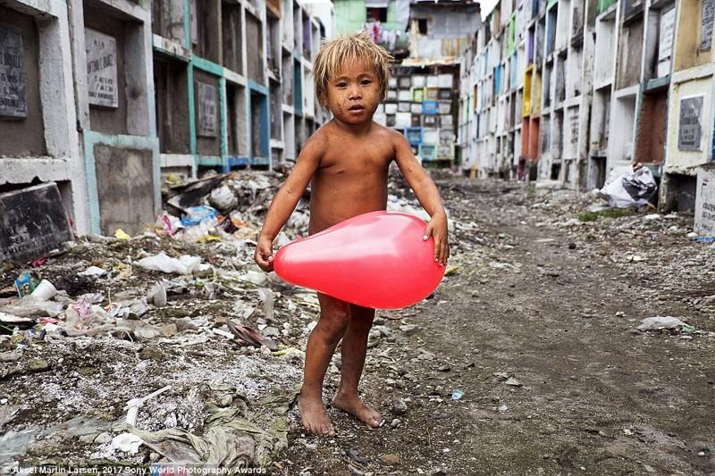 Портрет был сделан на кладбище в Маниле, Филиппины, где живет коммуна бездомных, включая и этого малыша. Он нашел среди костей воздушный шарик и теперь играет с ним в мире, дети, жизнь