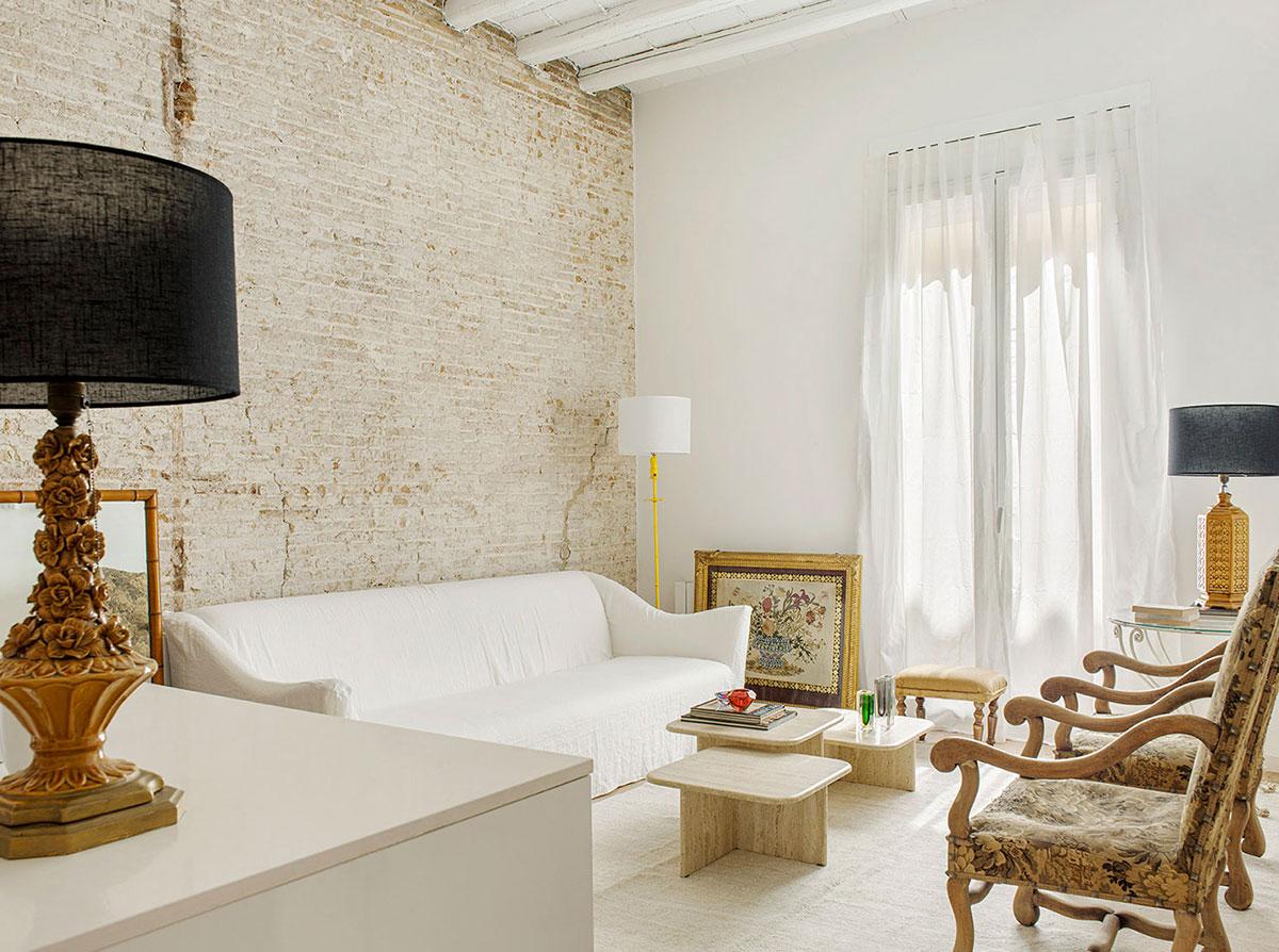 Белая квартира-студия с кирпичной стеной и антикварными креслами в Барселоне