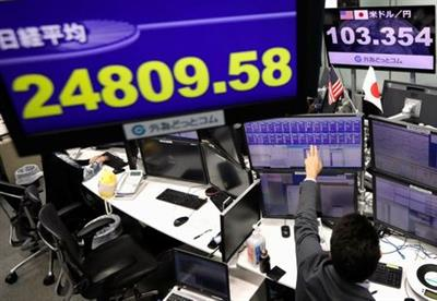An employee of the foreign exchange trading company works in front of monitors showing Japan's Nikkei share average and the Japanese yen exchange rate against the U.S. dollar at a dealing room in Tokyo, Japan November 9, 2020.  <div id=