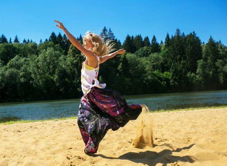 Девушка в восточных брюках, сшитых своими руками, бежит по песку