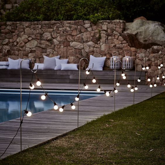 10 bistro bulb fairylights attached to hooks along the whole pool