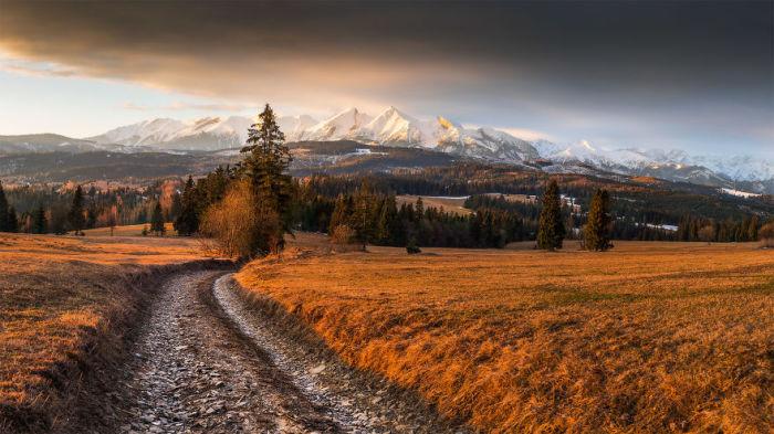 Дорога ведущая через равнины и озера к горным массивам.