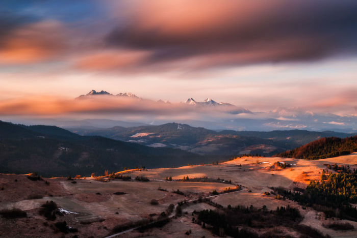 Разноцветные облака, подгоняемые ветром, бегут в сторону горных вершин.
