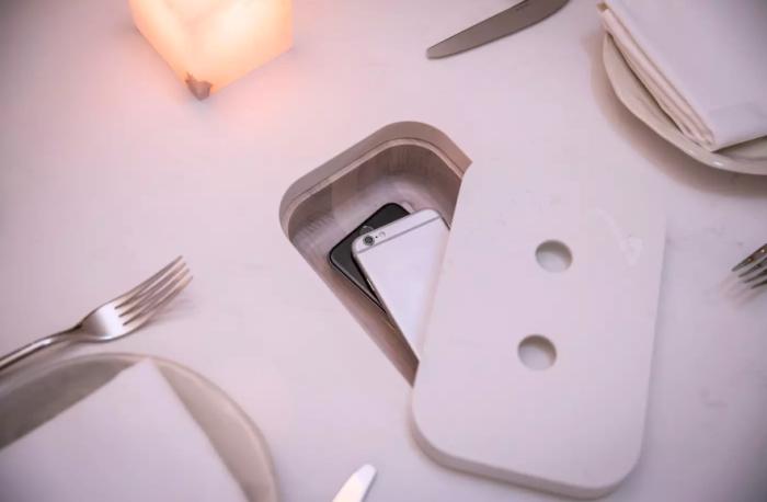 Даже для элитного ресторана Sara (Торонто) разработали специальные обеденные столы, где есть специальные ячейки для мобильных телефонов. | Фото: blogto.com.