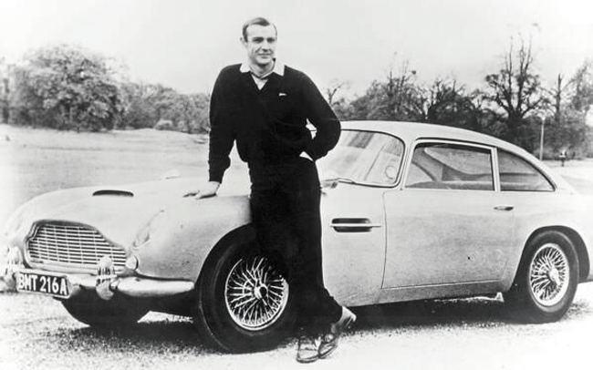 Шон Коннери в роли Джеймса Бонда позирует рядом с Aston Martin DB5, 1965 год